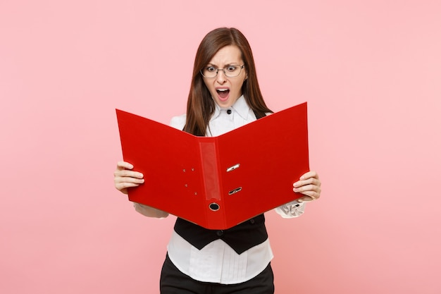 안경을 쓴 화난 젊은 비즈니스 여성은 파스텔 핑크색 배경에 격리된 서류 문서를 위해 빨간색 폴더를 보고 비명을 질렀다. 여사장님. 성취 경력 부 개념입니다. 광고 공간을 복사합니다.
