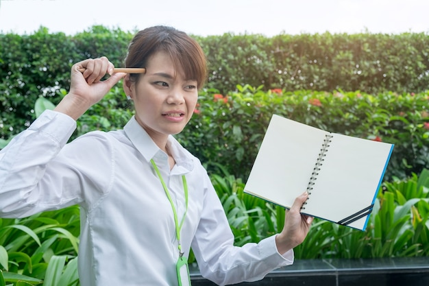 Young angry confused working woman face hold notebook and pencil point her head.