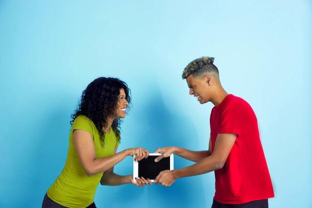 Giovani coppie arrabbiate in abiti casual in lotta per un tablet