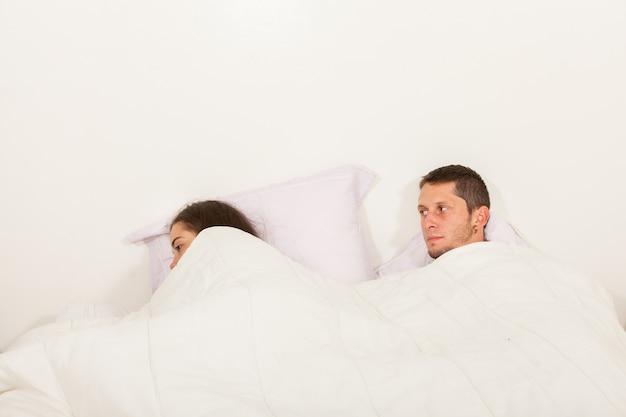 문제가있는 침대에서 서로 이야기하지 않는 젊은 화가 부부
