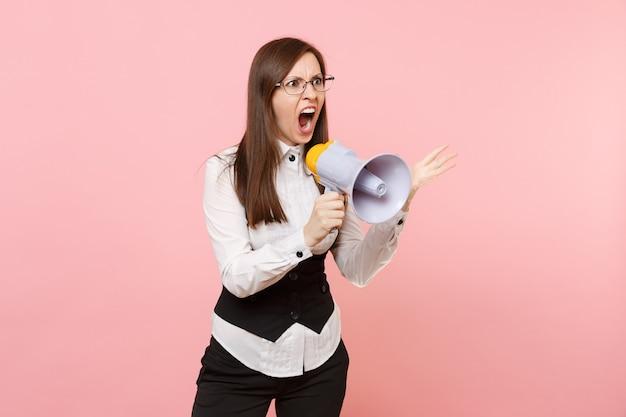 Молодой сердитый сумасшедший бизнес-леди в черном костюме и очках кричит, держа мегафон, раздвигая руки, изолированные на розовом фоне. леди босс. достижение карьерного богатства. скопируйте место для рекламы.