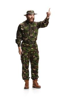 白いスタジオに分離された迷彩服を着ている若い怒っている猛烈な兵士