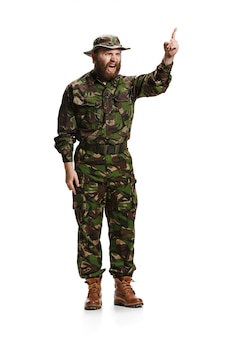 Young angry furious army soldier wearing camouflage uniform isolated on white studio