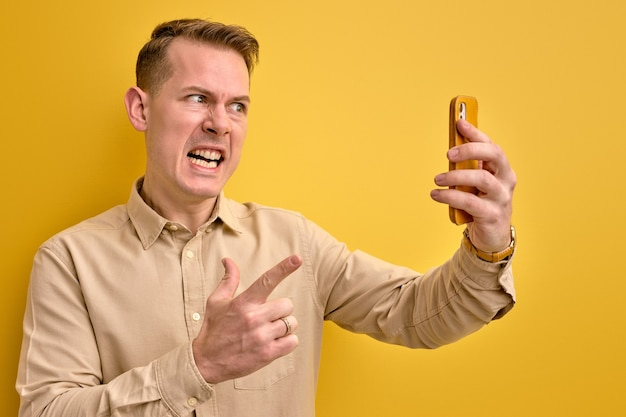 電話で話している間、携帯電話のカメラで叫んでいる若い怒っている男性、孤立した黄色の壁、側面図