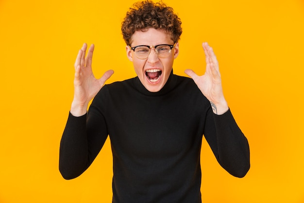 Young angry man in eyeglasses screaming with throwing up hands isolated on yellow