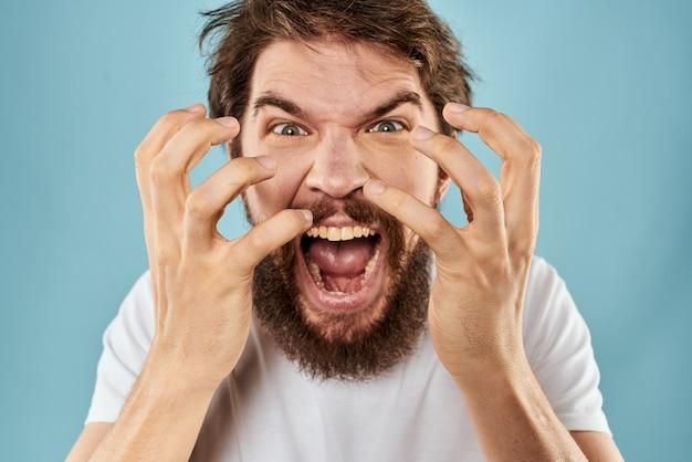 Молодой сердитый человек с бородой в белой футболке