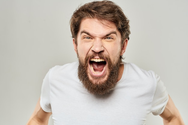 Young angry man with a beard in white t-shirt