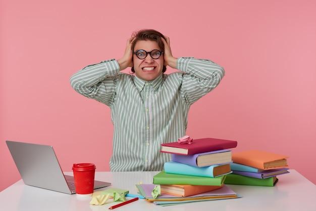 Giovane studente arrabbiato con gli occhiali, si siede al tavolo e lavora con il laptop, tiene la testa e sembra sorpreso, isolato su sfondo rosa.