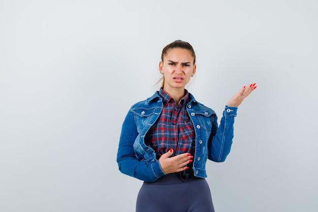 Giovane donna arrabbiata in camicia a scacchi, giacca, pantaloni e sguardo esitante, vista frontale.