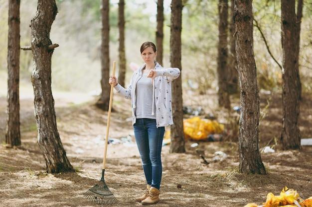 Молодая злая женщина, убирающая мусор с помощью граблей для сбора мусора, показывая большой палец вниз в замусоренном парке. проблема загрязнения окружающей среды. остановить мусор природы, концепция защиты окружающей среды.