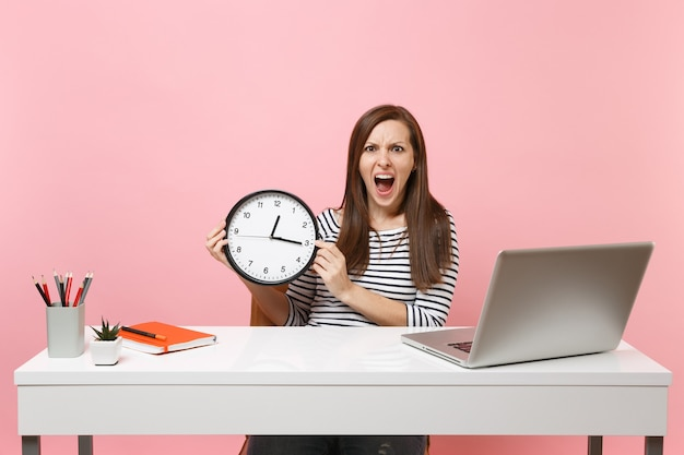 Young angry woman holding round alarm clock screaming while sit work at office with pc laptop