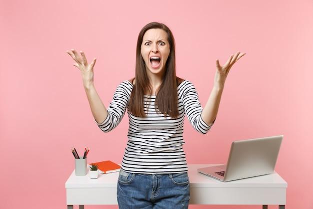 パステルピンクの背景に分離されたpcラップトップで白い机の近くに立って叫んで手を広げて働く若い怒っている女性。業績ビジネスキャリアコンセプト。広告用のスペースをコピーします。