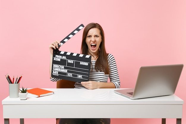 Young angry woman screaming holding classic black film making clapperboard and working on project while sit at office with laptop