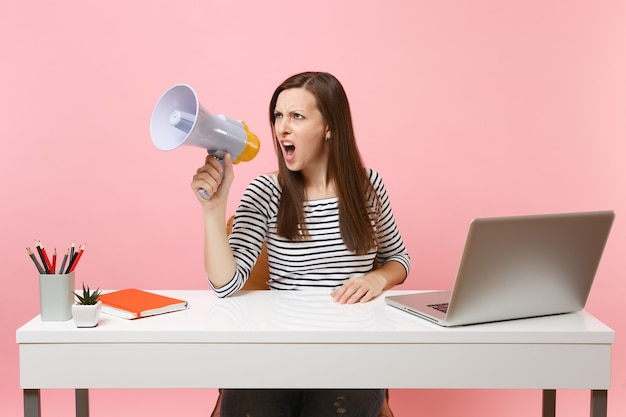 Young angry woman screaming in megaphone while sit, working on project at office with pc laptop