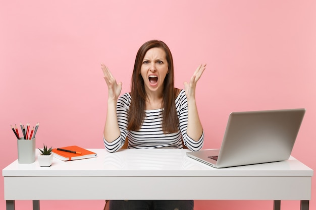 Young angry woman screaming spreading hand sit and work at white desk with contemporary pc laptop isolated on pastel pink background. achievement business career concept. copy space for advertisement.