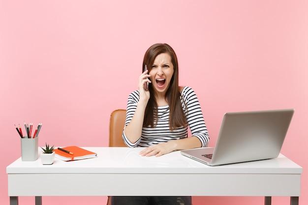 화난 젊은 여성은 파스텔 핑크색 배경에 격리된 pc 노트북을 들고 사무실에 앉아 프로젝트 작업을 하는 동안 휴대전화로 소리를 지르며 소리를 질렀다. 성취 비즈니스 경력 개념입니다. 공간을 복사합니다.