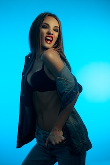 Young angry woman with red lips in jeans clothes screaming on blue