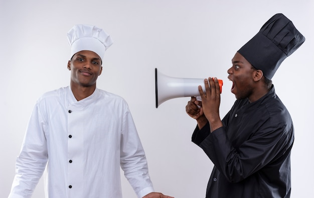 Young annoyed afro-american cook in black chef uniform shouts through loud speaker at confused cook in white chef uniform isolated on white background