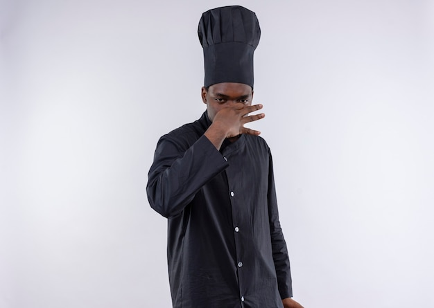 Il giovane cuoco afroamericano infastidito in uniforme del cuoco unico chiude il naso con la mano su bianco con lo spazio della copia