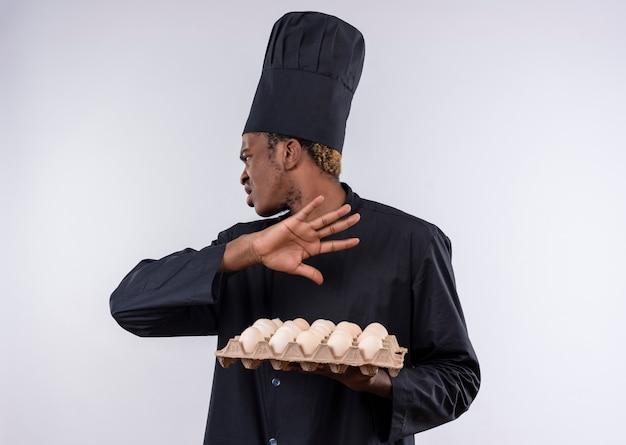 Giovane cuoco afro-americano infastidito in uniforme dello chef tiene lotto di uova e gesti vanno via segno di mano isolato su sfondo bianco con spazio di copia