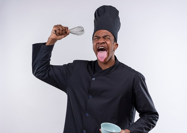 Young annoyed afro-american cook in chef uniform holds bowl and whisk tongue stucked out isolated on white background with copy space
