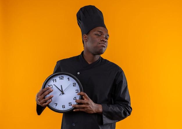 Il giovane cuoco afroamericano infastidito in uniforme del cuoco unico tiene l'orologio e guarda al lato sull'arancia con lo spazio della copia