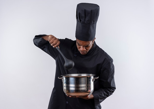 Young annoyed afro-american cook in chef uniform holds saucepan and spoon isolated on white background with copy space