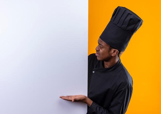 Il giovane cuoco afroamericano infastidito in uniforme del cuoco unico sta dietro la parete bianca e indica alla parete isolata su fondo arancio con lo spazio della copia