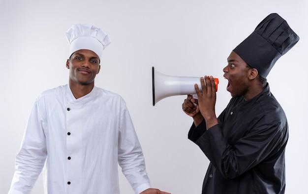 黒人シェフの制服を着た若いイライラしたアフリカ系アメリカ人の料理人は、白い背景で隔離の白いシェフの制服を着た混乱した料理人のスピーカーから叫びます