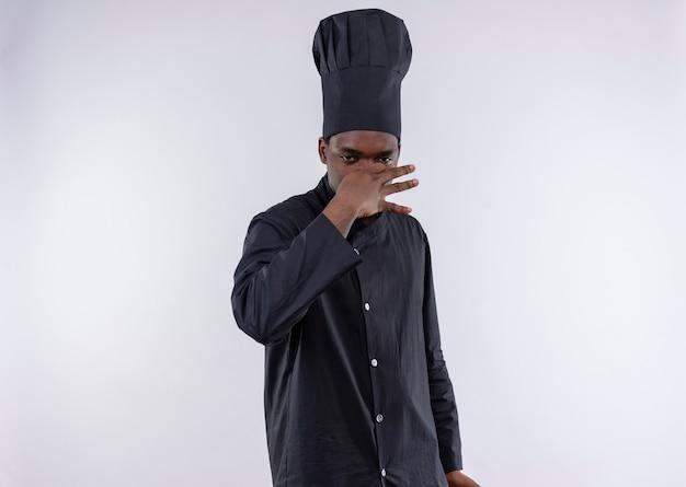 シェフの制服を着た若いイライラしたアフリカ系アメリカ人の料理人は、コピースペースで白の手で鼻を閉じます