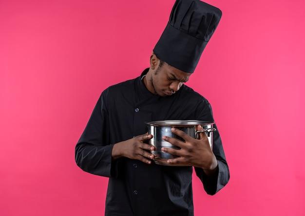 シェフの制服を着た若いイライラするアフリカ系アメリカ人の料理人は、コピースペースでピンクの背景に分離された鍋を保持し、見ています