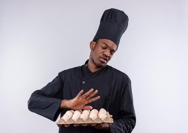 요리사 제복을 입은 젊은 화가 아프리카 계 미국인 요리사는 계란의 배치를 보유하고 복사 공간이 흰색 배경에 고립 멀리 밀어내는 척