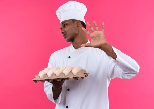 シェフの制服を着た若いイライラするアフリカ系アメリカ人の料理人は、新鮮な卵のバッチを保持し、コピースペースでピンクの背景に隔離された手でジェスチャーを遠ざけます