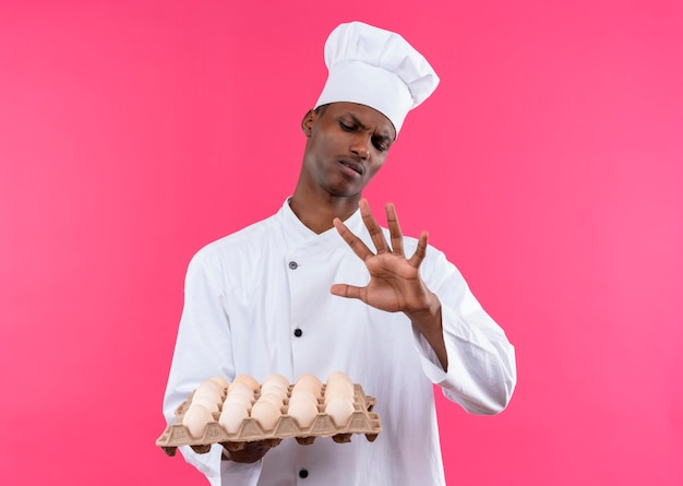 シェフの制服を着た若いイライラするアフリカ系アメリカ人の料理人は、新鮮な卵のバッチを保持し、コピースペースでピンクの背景に分離された彼の手を見てください