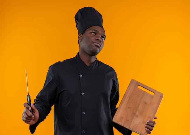シェフの制服を着た若いイライラしたアフリカ系アメリカ人の料理人は、コピースペースとオレンジ色のスペースで隔離された側を見てナイフとまな板を保持します