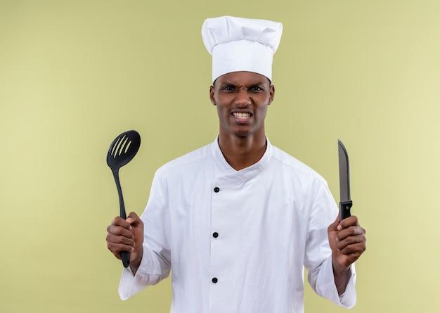 シェフの制服を着た若いイライラするアフリカ系アメリカ人の料理人は、コピースペースで緑の背景に分離されたナイフとヘラを保持します