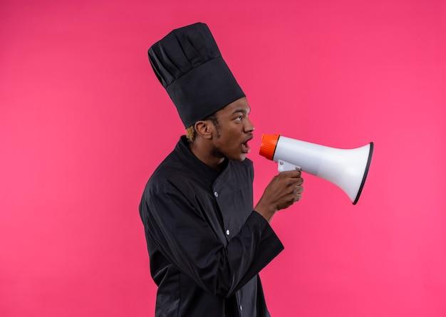 シェフの制服を着た若いイライラするアフリカ系アメリカ人の料理人は、コピースペースでピンクの背景に分離されたスピーカーを保持します