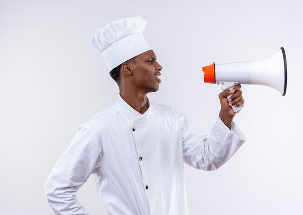 シェフの制服を着た若いイライラするアフリカ系アメリカ人の料理人は、コピースペースと白い背景で隔離のラウドスピーカーを保持します。