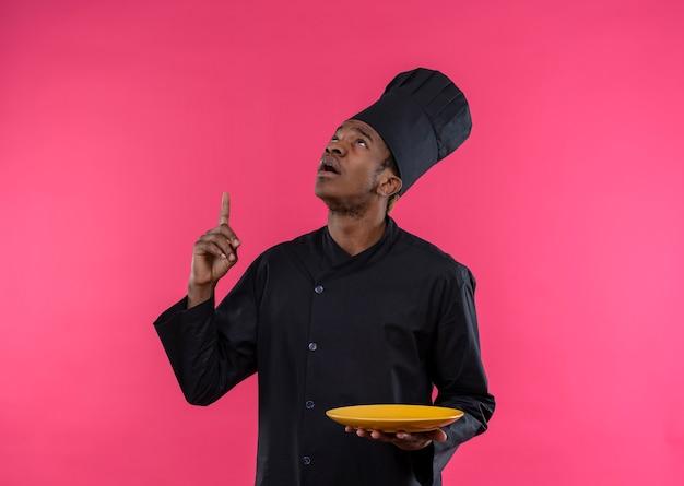 シェフの制服を着た若いイライラするアフリカ系アメリカ人の料理人は、プレートを保持し、コピースペースでピンクの背景に分離されたポイント