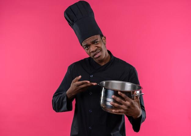 シェフの制服を着た若いイライラするアフリカ系アメリカ人の料理人は、コピースペースでピンクの背景に分離された手で鍋とポイントを保持します