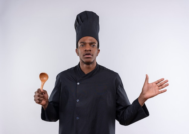 シェフの制服を着た若いイライラするアフリカ系アメリカ人の料理人は木のスプーンを保持し、コピースペースと白い背景で隔離の手を保持します。