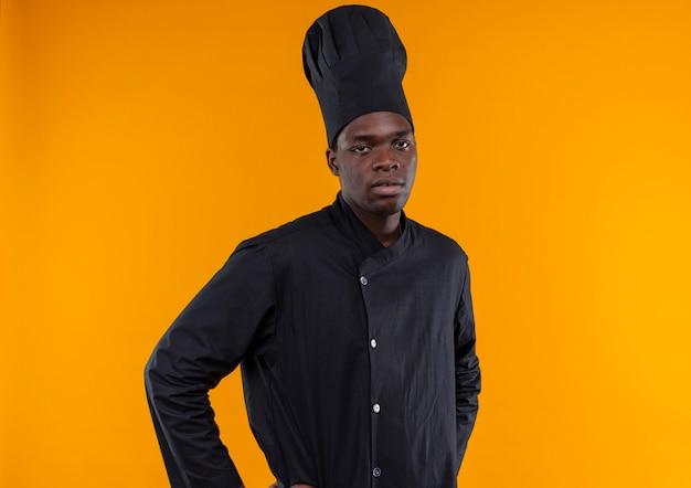 シェフの制服を着た若いイライラするアフリカ系アメリカ人の料理人は腰に手を置き、コピースペースでオレンジ色の背景に分離されたカメラを見る