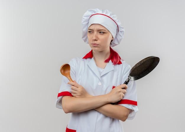 Il giovane chef femminile biondo infastidito in uniforme del cuoco unico attraversa le braccia e tiene la padella e il cucchiaio isolati sulla parete bianca