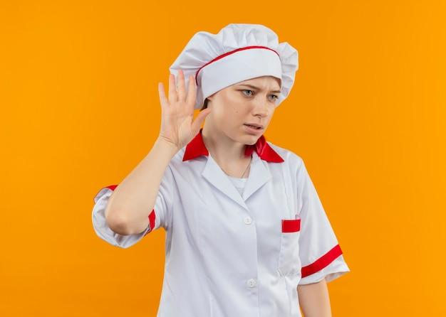 Il giovane chef femminile biondo infastidito in gesti uniformi del cuoco unico non può sentire il segno isolato sulla parete arancione