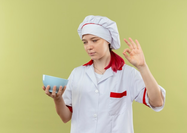 Il giovane chef femminile biondo infastidito in uniforme del cuoco unico tiene la ciotola e gesti il segno giusto della mano che rotola gli occhi isolati sulla parete verde