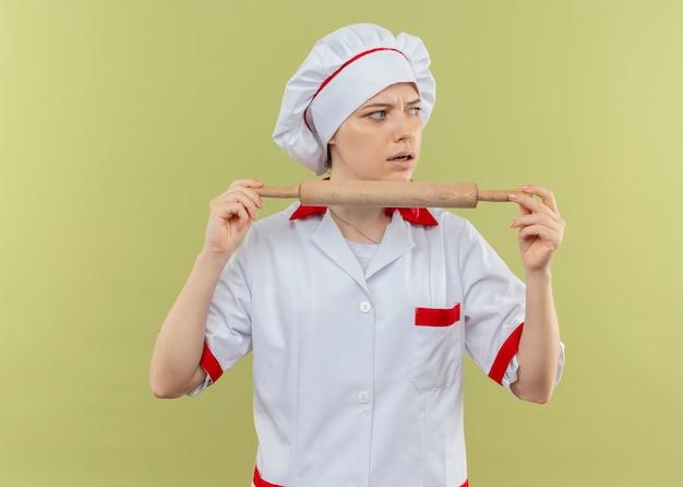 Il giovane chef femmina bionda infastidito in uniforme da cuoco tiene il mattarello e guarda il lato isolato sulla parete verde