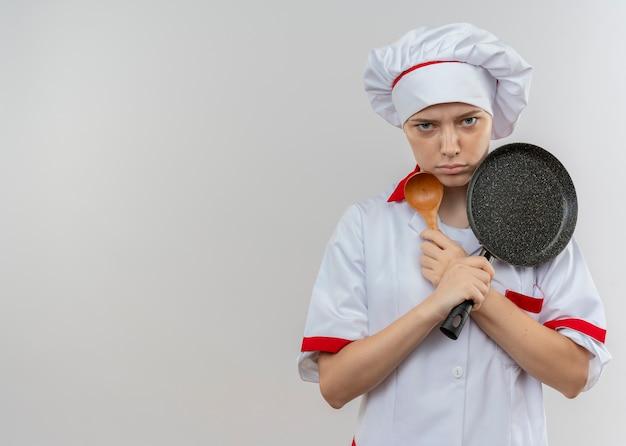 Молодая раздраженная блондинка-шеф-повар в униформе скрещивает руки и держит сковороду и ложку, изолированные на белой стене