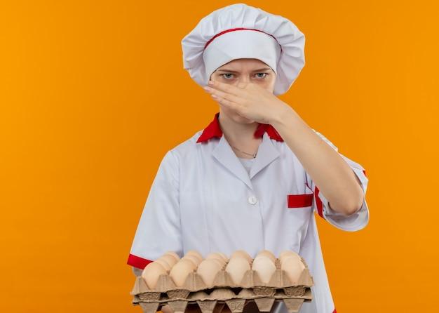 シェフの制服を着た若いイライラする金髪の女性シェフは、卵のバッチを保持し、オレンジ色の壁に隔離された手で鼻を閉じます