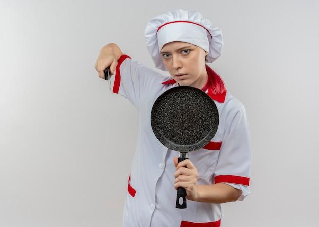シェフの制服を着た若いイライラする金髪の女性シェフは、白い壁に分離されたフライパンとナイフを保持します。