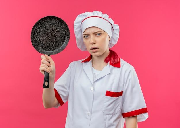 シェフの制服を着た若いイライラする金髪の女性シェフはフライパンを保持し、ピンクの壁に孤立しているように見える